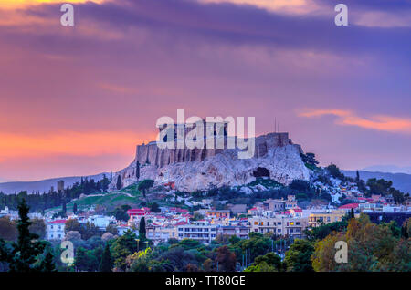 The Acropolis of Athens city in Greece with the Parthenon Temple (dedicated to goddess Athena) as seen from the Panathenaic Stadium, at sunset time - Stock Photo