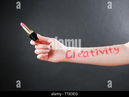 Word creativity written on female hand on black background - Stock Photo