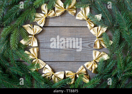 Christmas card concept with fir tree branches and a circle of golden bows on wooden background - deep shadows, text space - Stock Photo