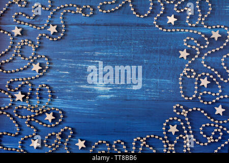 Christmas decoration with silver bead chain and stars on dark blue wooden background - place for text in the middle - Stock Photo