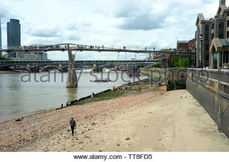 Low tide on the River Thames, exposing river bank. The Millennium Bridge and London Blackfriars station and bridge visible in background. London, UK. - Stock Photo
