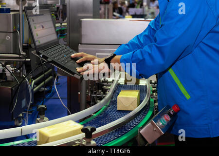 manufacturing engineer used computer to control product inspection system automation machine in modern factory while products are moving on the convey - Stock Photo