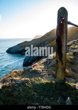 A setting sun shining through a hole on a handrail on the coastal path between Langland Bay and Caswell Bay on Gower, Wales, UK. - Stock Photo