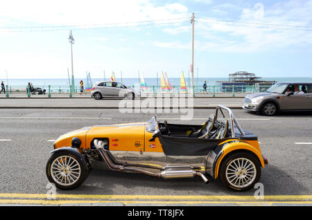Brighton, UK - August 14, 2016: Beautiful yellow vintage Lotus Cobra car parked in the Brighton beach avenue with rests of Brighton's old West Pier. - Stock Photo