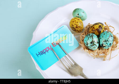 Easter table setting with card and Easter eggs on color wooden background - Stock Photo