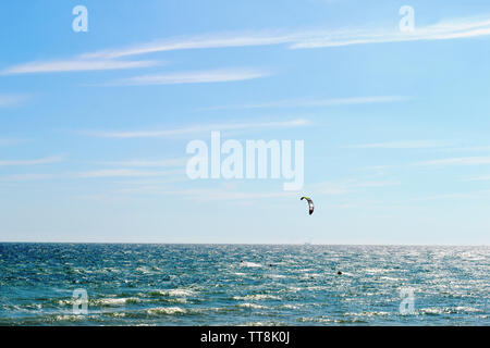 Beautiful seascape view in backlit and kitesurfing in Brighton, England. - Stock Photo