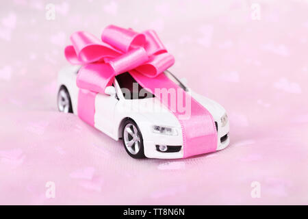 New car with bow as present  on pink background - Stock Photo