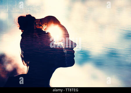 Silhouette of woman head with sun in head. Philosophy and psycology female multi exposure concept. - Stock Photo