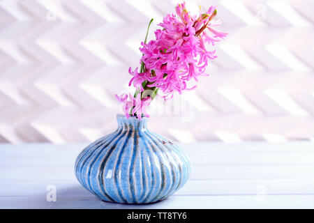 Beautiful hyacinth flower in vase on wooden table - Stock Photo