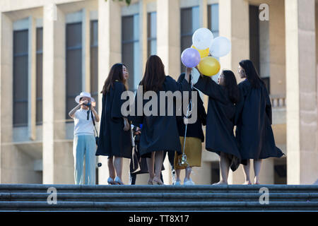 A group of graduating students pose for photos in Red Square at the University of Washington on June 11, 2019. - Stock Photo