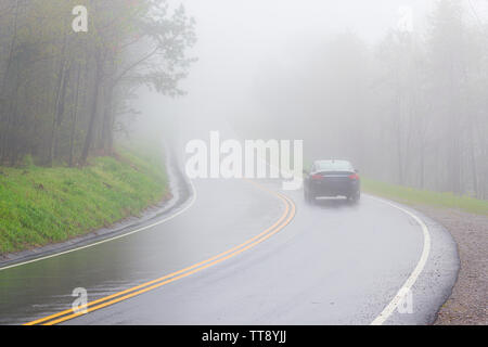 Horizontal shot of a car disappearing into dense Smoky Mountain fog with copy space. - Stock Photo