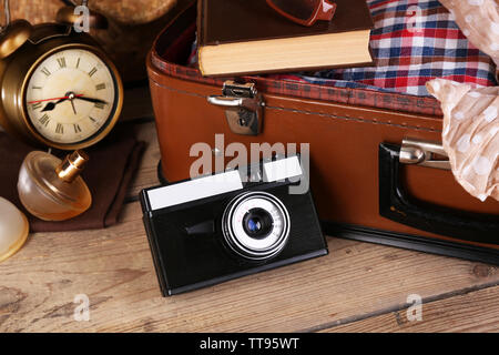 Packing suitcase for trip on wooden background - Stock Photo