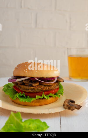 Homemade mushroom veggie burger on white wooden background with copy space. - Stock Photo