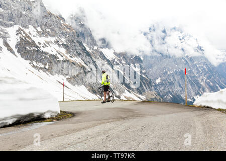 Male cyclist stops to admire the dramatic Swiss Alpine mountain landscape on the way down the Grosse Scheidegg pass towards Grindelwald - Stock Photo