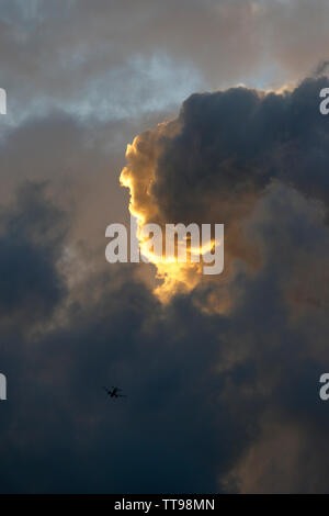 Sunset cloudscape showing grey clouds and colours from the sun which is below the horizon. - Stock Photo