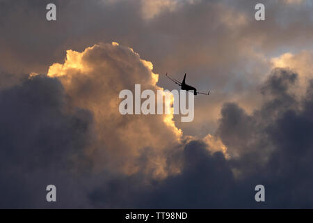 Sunset cloudscape showing grey clouds and colours from the sun which is below the horizon. Plus an airliner departing Stansted airport Essex - Stock Photo