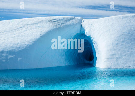 On the Matanuska Glacier, a large ice cave cuts into the glacier ice but its entrance is flooded by a deep blue pool.