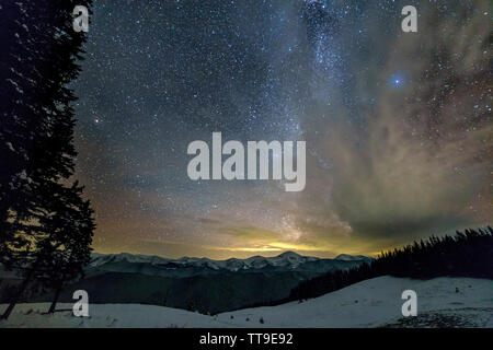 Mountain winter night panorama after sunset. Steep long ridge mountain peaks, deep snow in valley, hills covered with dense spruce forest, dramatic sn - Stock Photo