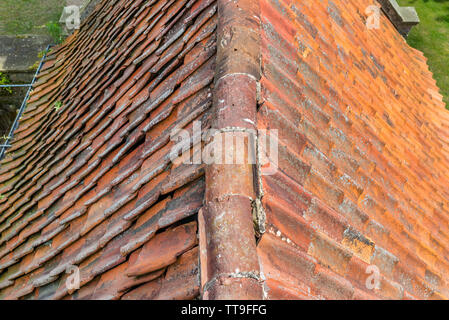 A red ceramic roof tile placed on an old building, photos taken up close. - Stock Photo