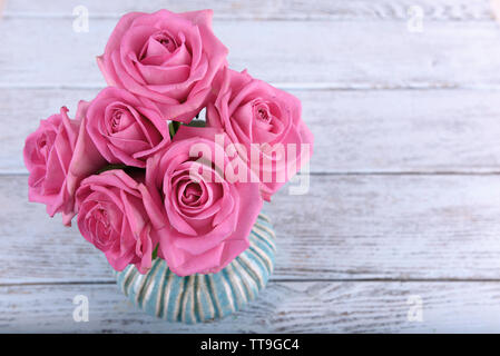 Beautiful pink roses in vase on wooden background - Stock Photo