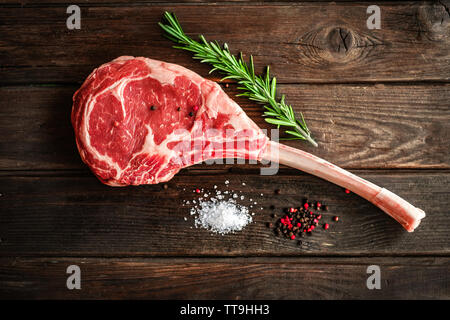raw Tomahawk steak on wooden background with spices for grilling - Stock Photo