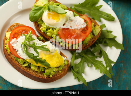 Tasty sandwiches with egg, avocado and vegetables on plate, on wooden background - Stock Photo