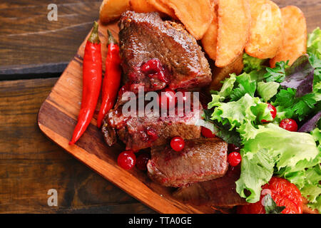Beef with cranberry sauce, roasted potato slices on cutting board, on wooden background - Stock Photo