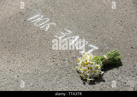 Beautiful bouquet of daisies on asphalt outdoors - Stock Photo