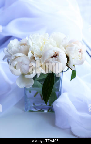 Beautiful white peonies in vase on fabric background - Stock Photo