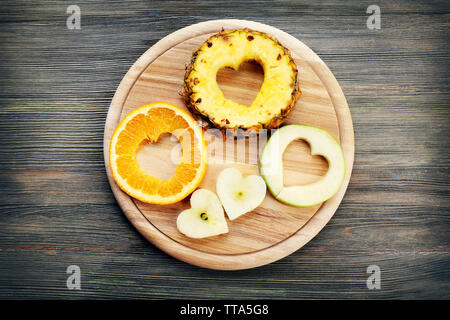 Fruits slices with cut in shape of heart on wooden background - Stock Photo