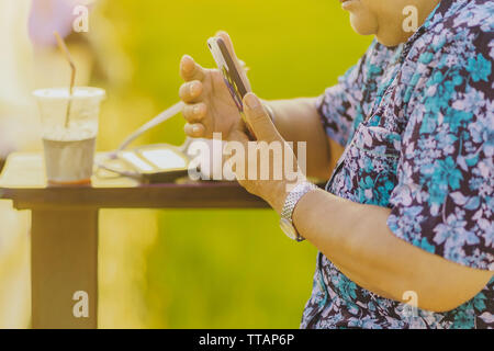 Elderly woman sit for resting and waiting for time to take photos of the sunset on the farmer's balcony in the rice fields.