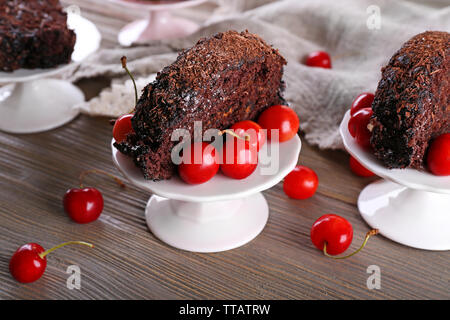 Delicious chocolate roll with cherries in saucer on wooden background - Stock Photo