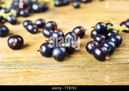 Ripe black currants on wooden background - Stock Photo