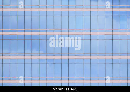 modern office building elevation. glass curtain wall repeating pattern reflecting cloud in the sky. city people in the architectural box. - Stock Photo