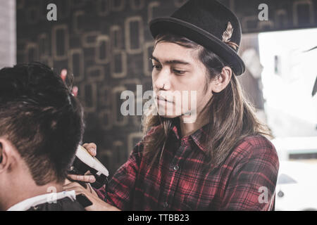 portrait of professional Asian man with long brown hair work as barber trimming his costumer with electric clipper machine in barbershop - Stock Photo