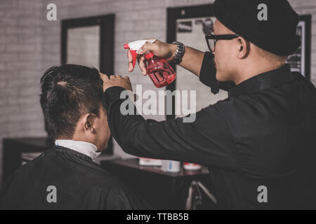 Rearview of barber or hairdresser sprinkles water with water spray on the client's hair in a  vintage barbershop with right hand - Stock Photo