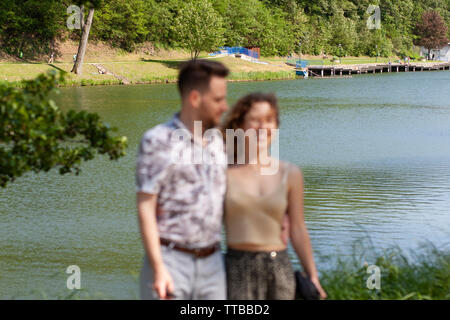 Young couple want to take a photo of them by a tourist, but inexpert and the picture is out of focus and decomposed - Stock Photo