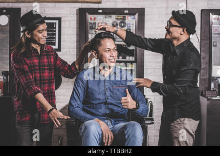 portrait of happy two barber with client standing and smiling at barberhop, hairstylisy and costumer interaction concept - Stock Photo