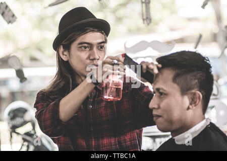 portrait of barber or hairdresser sprinkles water with water spray on the client's hair in a  vintage barbershop with right hand - Stock Photo