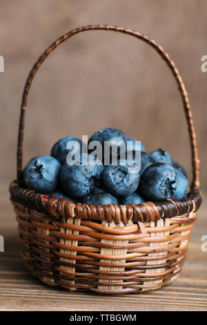 Tasty ripe blueberries in basket on wooden table close up - Stock Photo