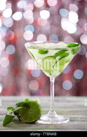 Glass of cocktail with ice on blurred lights background - Stock Photo