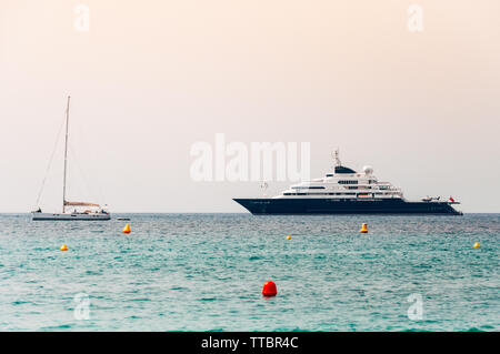 Huge yacht and a small sailing boat in Cannes, France - Stock Photo