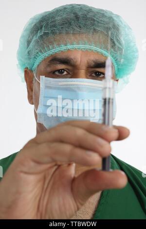 Male surgeon holding a syringe - Stock Photo