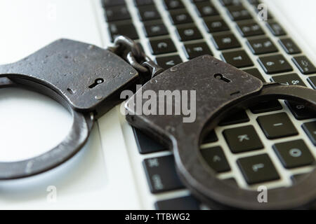 Metal handcuffs over a laptop - studio shot - Stock Photo