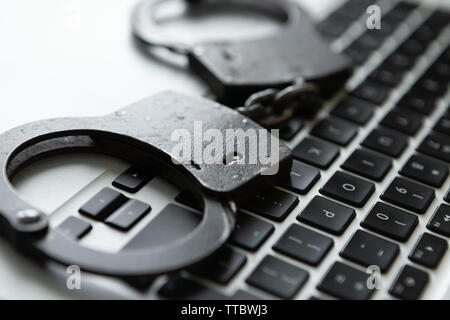 Hetal handcuffs over a laptop - studio shot - Stock Photo