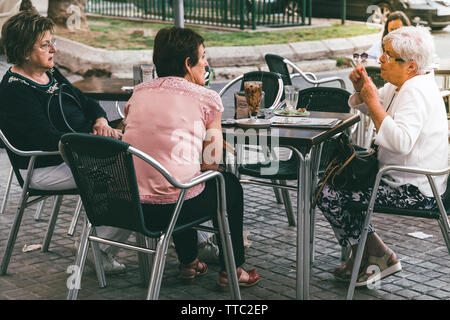 Valencia, Spain - June 1, 2019: Three elderly woman  eating ice cream on terrace. Friendship through the years. - Stock Photo