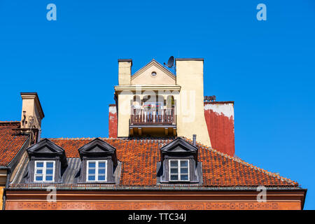 Traditional historic tenement house attic exterior isolated against blue sky, one with small balcony, windows in red tiled roof in Old Town of Warsaw - Stock Photo