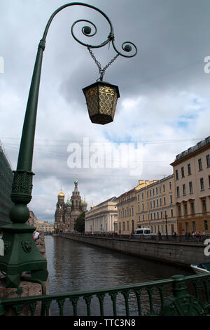 St Petersburg Russia, view of Griboedov canal from bridge with orate lamp post with the Church of the Savior on Spilled Blood in background - Stock Photo