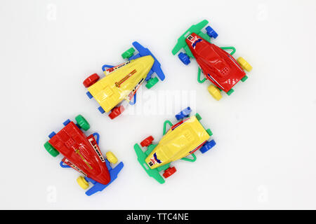Four vintage collectable plastic racing toy car, isolated on white background, close-up - Stock Photo