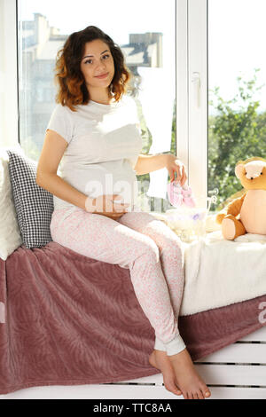 Pregnant woman on window board with baby booties and teddy bear in the room - Stock Photo